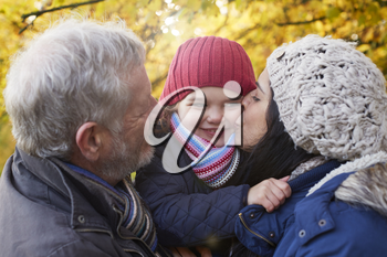 Mother And Grandfather Cuddle Girl On Autumn Walk