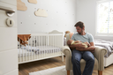Father Sitting In Nursery Chair Holds Sleeping Baby Son