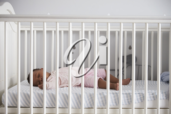 Side View Of Baby Girl Sleeping In Nursery Cot