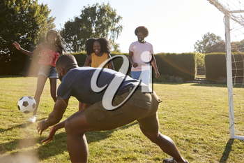Four black adult friends having a fun game of football
