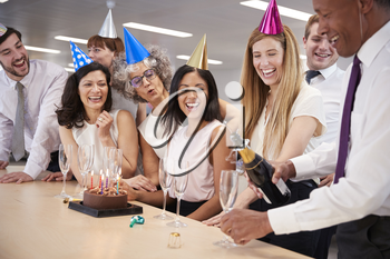 Colleagues celebrating a birthday in office pour champagne