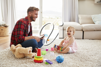 Father and young daughter playing toy instruments at home