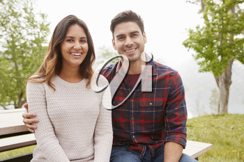 Young smiling couple sit embracing in a park