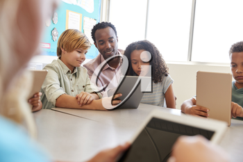 Teacher sits with young kids using computers in school class