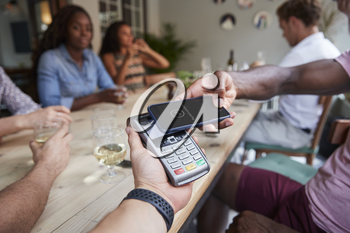 Close Up Of Customer In Restaurant Paying Bill With Contactless Phone App