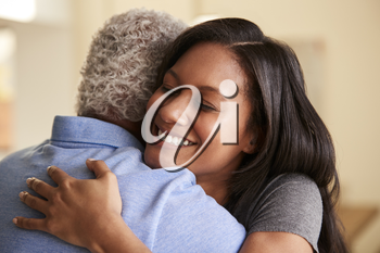 Over The Shoulder View Of Senior Father Being Hugged By Adult Daughter At Home
