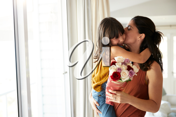 Mid adult woman holding her daughter, who's given her a bunch of flowers on her birthday, waist up