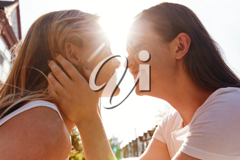 Female Gay Couple Outside House About To Kiss Against Flaring Sun