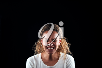 Studio Portrait Of Angry Woman Shouting At Camera Against Black Background