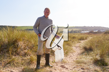 Portrait Of Senior Man Collecting Litter On Winter Beach Clean Up