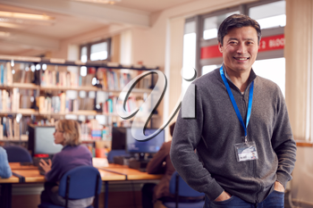 Portrait Of Mature Male Teacher Or Student In Library With Other Students Studying In Background