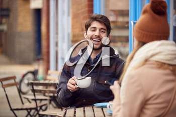 Couple On Date Sitting Outside Coffee Shop On Busy City High Street Looking At Digital Devices