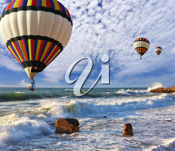 Huge balloons with the passenger basket flying over the sea shore. Mediterranean Sea, a spring storm