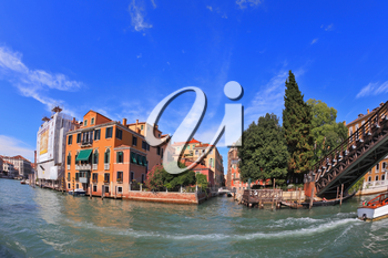 Wonderful holiday in Venice. Ornate facades perfectly restored antique palaces lit setting sun. Graceful bridge spans the Grand Canal.  Photo making the lens Fisheye