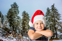 Charming eight-year boy in Santa Claus hat smiling.  Pine forest in mountains are covered with the first snow