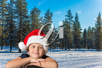 New Years is soon. A handsome boy in a red Santa Claus hat is smiling. Winter forest in the snow