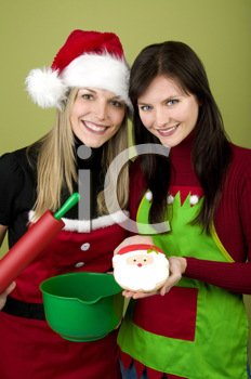 Royalty Free Photo of Women Holding Baking Utensils and a Santa Cookie