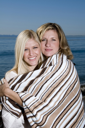 Royalty Free Photo of Two Women on the Beach Keeping Warm in a Towel