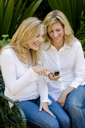 Royalty Free Photo of Women on a Park Bench Looking at a Camera Phone