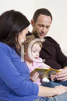 Royalty Free Photo of a Couple Reading to Their Daughter