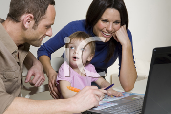 Royalty Free Photo of a Couple Playing on a Laptop With Their Baby