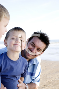 A man with his two sons at the beach