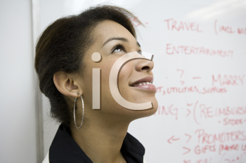Royalty Free Photo of a Businesswoman Beside a Whiteboard Looking Up