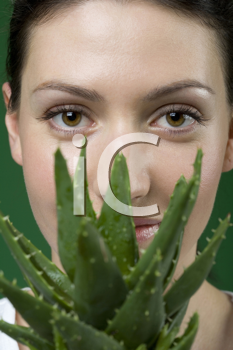 Royalty Free Photo of a Woman Holding an Aloe Vera Plant