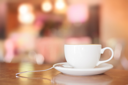 White Coffee Cup on brown wooden table with bokeh