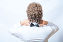 Bow tie on the back side. Strangeness or fun concept. Back view of an elegant young fashion man in tuxedo on gray background, toned image. Touch bow tie by hands.