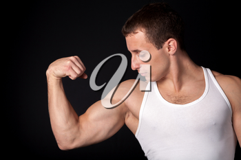 a male in white tank top with strong muscles on the black background