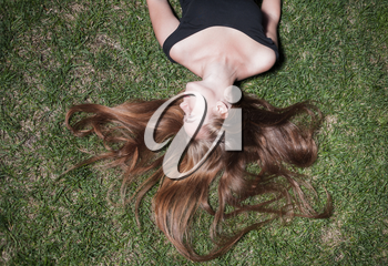 Smiling woman laying on grass. Beautiful young girl is lying on green grass in the evening time. The girl lays on a grass of a meadow.
