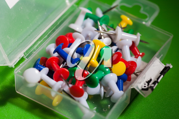 closeup shot of mixed colors office push-pins in the open plastic pack, angle view, on the green background