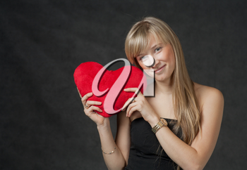 Pretty blond haired women with her heart in hands. Beautiful young woman holding a heart shaped red pillow and smiling