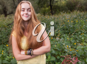 Front view of the smiling blond girl. Female against nature background
