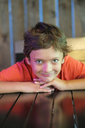 Smiling boy sitting in restaurant with his chin on hands