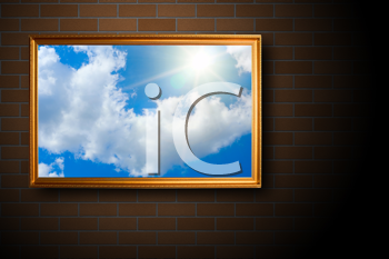 blue sky picture at gold frame on brick wall background