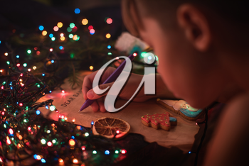 Boy writes a letter to Santa, cristmas background