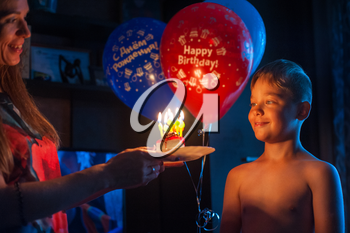 mother congratulates her son with birthday, gives cake with candles