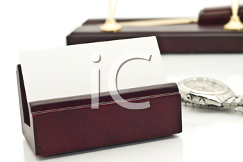 Close-up of Card holder with blank white business card, pens, and watch on stand over white