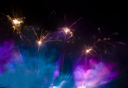 Fireworks in the lilac and blue smoke at night in the sky useful as festive background