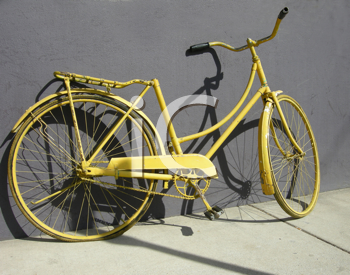 Royalty Free Photo of an Old Yellow Bike Leaning Against a Wall