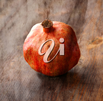 Vintage image with old dry pomegranate on wood background