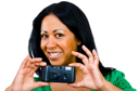 Portrait of a woman photographing with a camera and smiling isolated over white