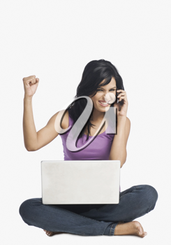 Woman talking on a mobile phone and clenching fist
