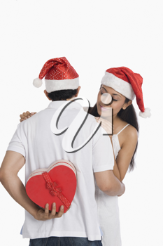 Man hiding a Christmas present to surprise his girlfriend