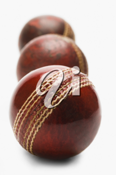 Close-up of old and new cricket balls in a row