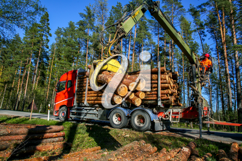 Crane in forest loading logs in the truck. Crane operator loading logs on to truck on a nice spring day. Timber harvesting and transportation in forest. Transport of forest logging industry and forestry industry.