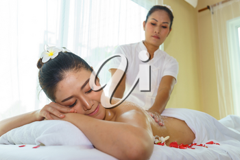 Middle aged Asian female massage therapist is performing massage to young Asian female customer.