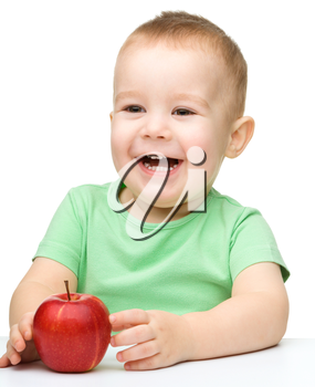 Portrait of a cute cheerful little boy, who is smiling while sitting at table with apple, isolated over white